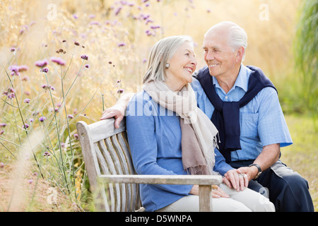 Older couple relaxing on park bench - Stock Photo