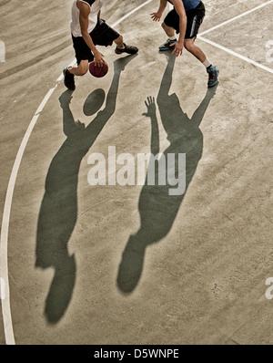 Men playing basketball on court - Stock Photo