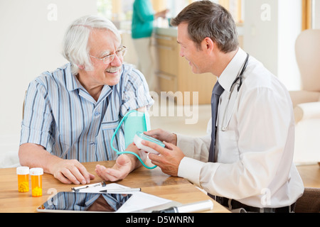 Doctor testing older patient's blood pressure at house call - Stock Photo