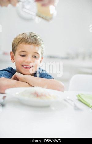 Smiling boy having spaghetti at table - Stock Photo