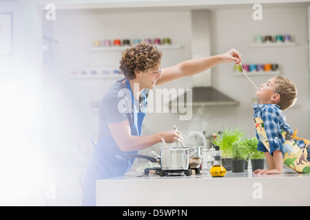 Father and son cooking in kitchen - Stock Photo