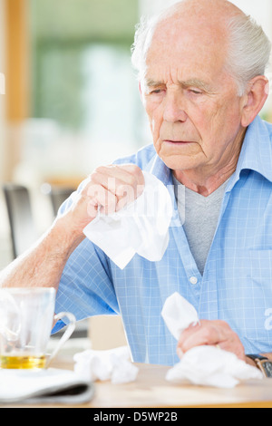 Older man with cold wiping his nose - Stock Photo