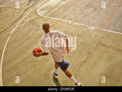 Man playing basketball on court - Stock Photo