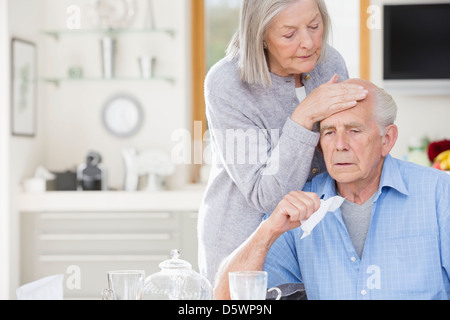 Older woman feeling sick husband's forehead - Stock Photo