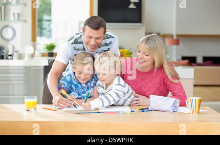 Family coloring together at table - Stock Photo