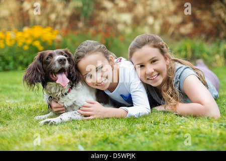 Smiling girls relaxing with dog on lawn - Stock Photo