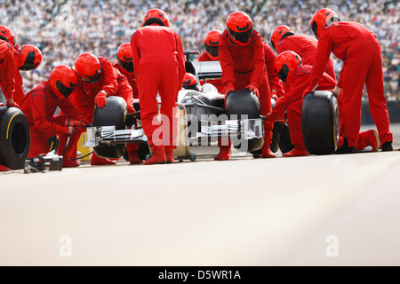 Race car team working at pit stop - Stock Photo