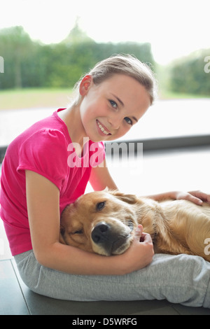 Girl relaxing with dog on floor - Stock Photo