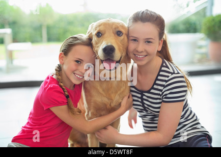 Smiling girls hugging dog indoors - Stock Photo