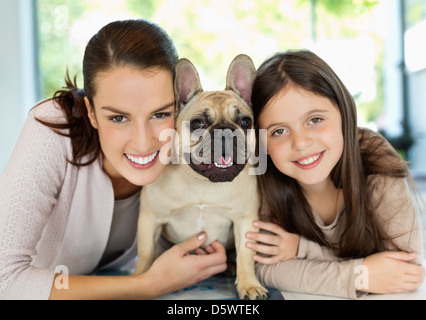 Smiling mother and daughter hugging dog - Stock Photo
