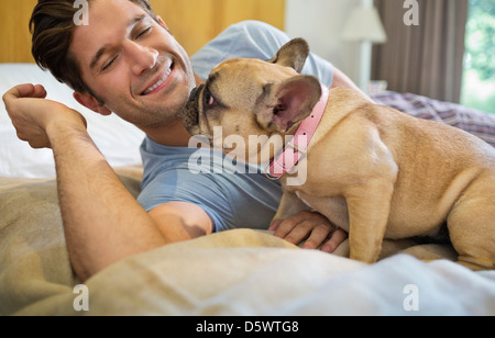 Dog licking man's face on bed - Stock Photo