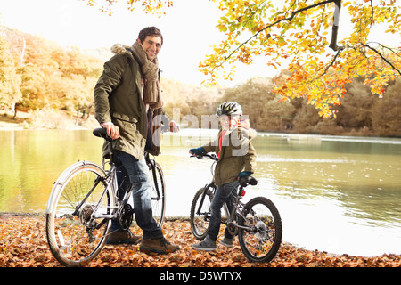 Father and son sitting on bicycles in park - Stock Photo