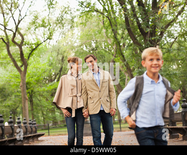 Family walking together in park - Stock Photo
