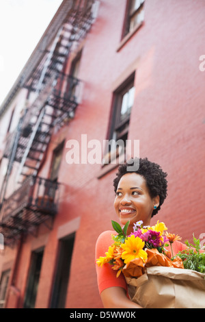 Woman carrying bag of flowers on city street - Stock Photo