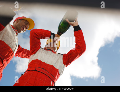 Racer drinking champagne on track - Stock Photo