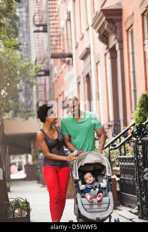 Family walking together on city street - Stock Photo