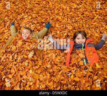 Children laying in autumn leaves - Stock Photo