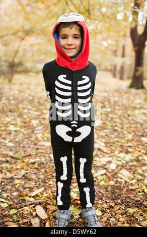 Boy wearing skeleton costume in park - Stock Photo