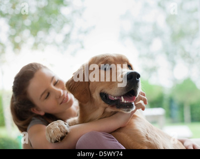 Smiling girl hugging dog outdoors - Stock Photo