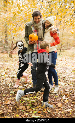 Couple with children in skeleton costumes in park - Stock Photo