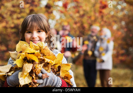 Girl playing with autumn leaves in park - Stock Photo