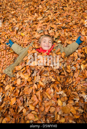 Boy laying in autumn leaves - Stock Photo