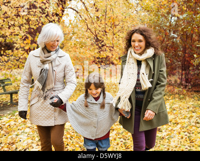 Three generations of women walking in park - Stock Photo