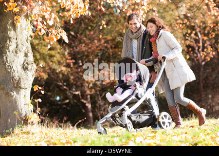 Couple pushing baby in stroller in park - Stock Photo