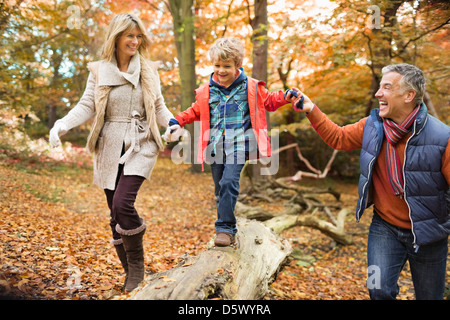 Family walking on log in park - Stock Photo