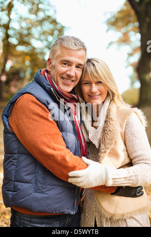 Older couple hugging in park - Stock Photo