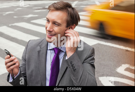 Businessman talking on cell phone on city street - Stock Photo
