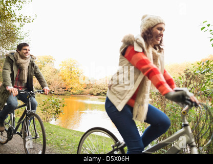 Couple riding bicycles in park - Stock Photo
