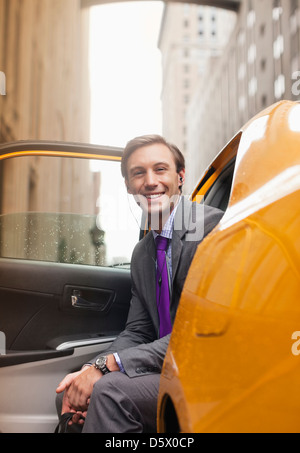 Businessman sitting in taxi on city street - Stock Photo