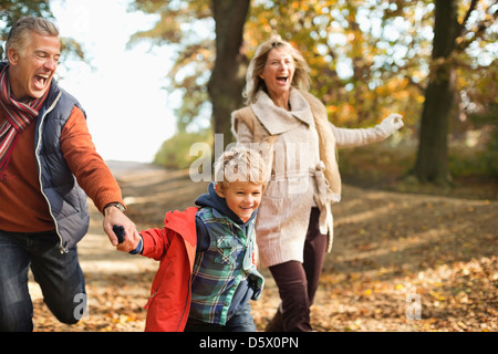 Boy and grandparents walking in park - Stock Photo