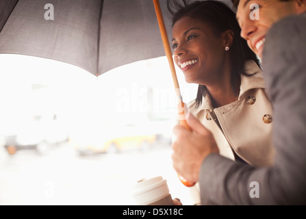 Businesspeople huddled under umbrella - Stock Photo