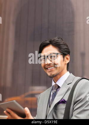 Businessman using tablet computer on city street - Stock Photo