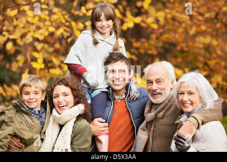 Family smiling together in park - Stock Photo
