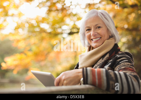 Older woman using tablet computer outdoors - Stock Photo