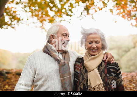 Older couple walking together in park - Stock Photo
