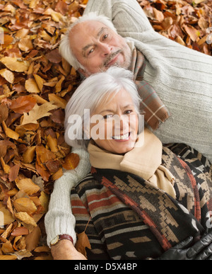 Older couple laying in autumn leaves - Stock Photo