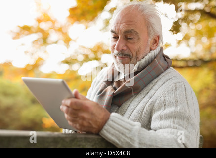 Older man using tablet computer in park - Stock Photo