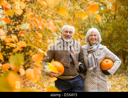 Older couple carrying pumpkins in park - Stock Photo