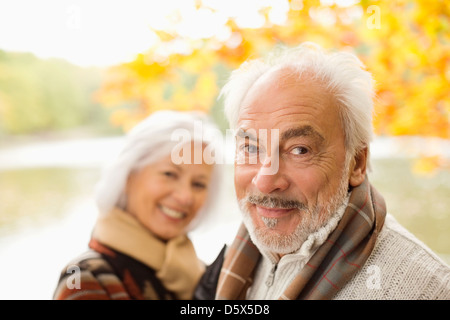Older couple standing in park - Stock Photo