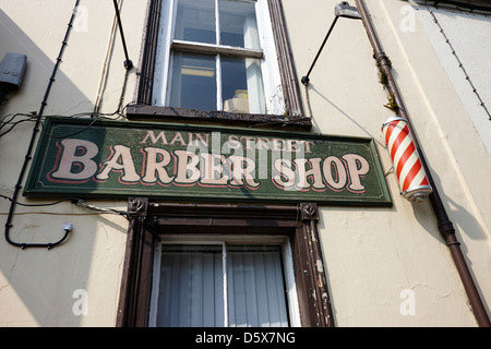 worn paint on painted sign outside traditional barber shop moira county down northern ireland uk - Stock Photo
