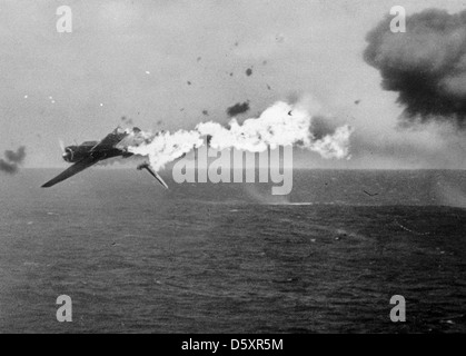A Japanese torpedo bomber goes down in flames after a direct hit by 5-inch shells from the USS YORKTOWN (CV-10), - Stock Photo