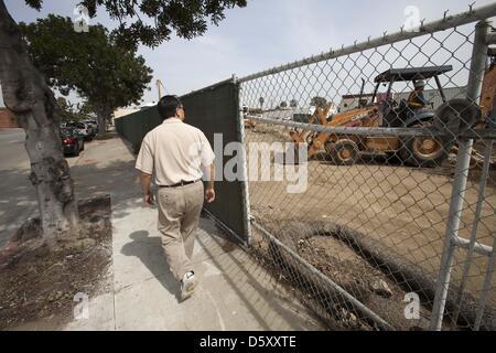 March 25, 2013 - Los Angeles, California, U.S - A pedestrian walks by as a Gas Company worker with a heavy machinery - Stock Photo