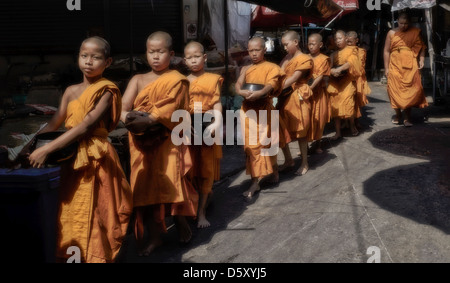 A group of novice Thai Buddhist monks collecting alms. Thailand South East Asia. - Stock Photo