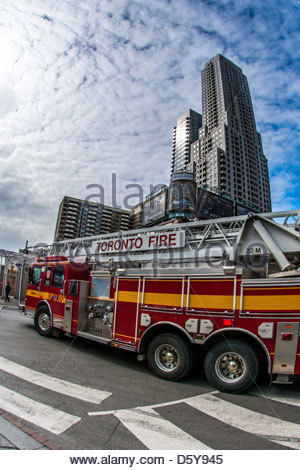 Fire truck at Yonge and Bloor in Toronto speeding to quench a fire - Stock Photo
