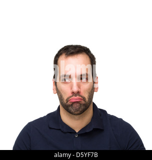 Portrait of a young man pouting while looking to the side - Stock Photo