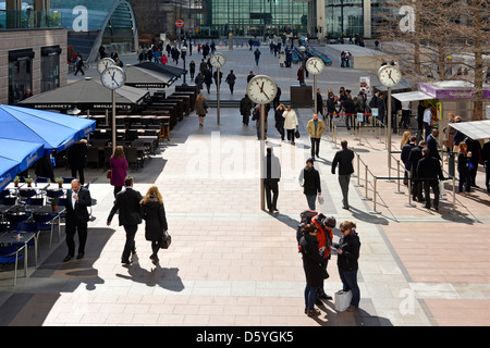 Canary Wharf clocks on the plaza with office workers at lunchtime Docklands Tower Hamlets East London England UK - Stock Photo